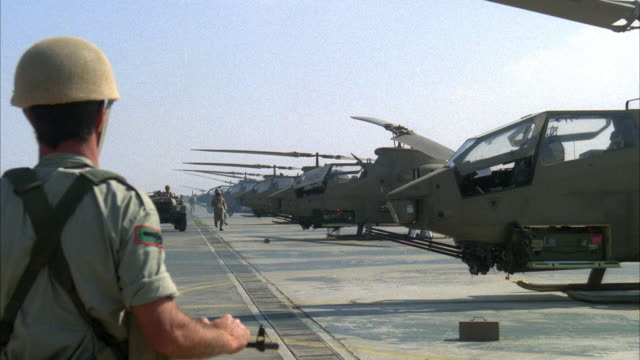 stockvideo's en b-roll-footage met medium angle of an air base with several military helicopters lined up. see back of partially blocked soldier in foreground. then see pilots run over to respective helicopters. - luchtmacht