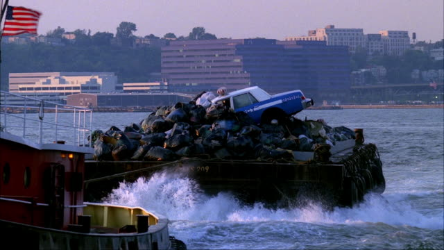 medium angle tracking shot of red tugboat with american flag pulling barge with junk or garbage, appears from right and moves across to left. focuses on police car on top of garbage bags on barge. tugboat turns and exits frame to right. - barge stock videos & royalty-free footage
