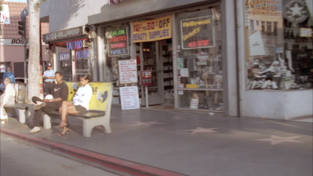 vídeos de stock e filmes b-roll de medium angle moving pov of city street or hollywood blvd and hollywood walk of fame. see walk of fame stars in sidewalk. see storefronts and pedestrians. - bulevar