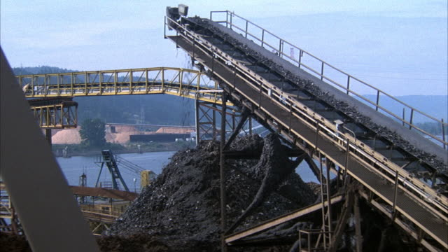 close angle of upward ramp belt carrying metal pieces. metal pieces fall off ramp when reach top. metal pile below ramp, crane, machines next to ramp. river and mountain in bg. - gürtel stock-videos und b-roll-filmmaterial