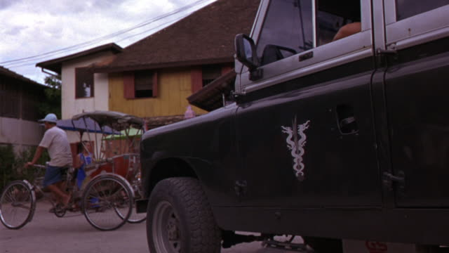 medium angle of military vehicle or jeep with insignia of intertwined dragons. resembles caduceus. pedicab seen. as jeep drives away, children with water guns and two story asian hut style building are seen. - hermesstab stock-videos und b-roll-filmmaterial