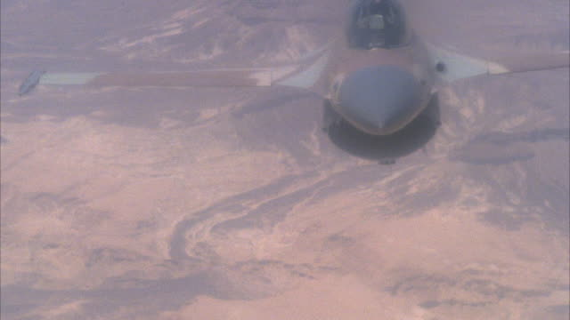 TRACKING SHOT OF A CAMOUFLAGE F-16 FIGHTER JET FLYING. POV IS OF FRONT OF JET. SEE ANOTHER JET IN BACKGROUND PERFORMING DOGFIGHT MANEUVERS. SEE LAND BELOW. ACTION.