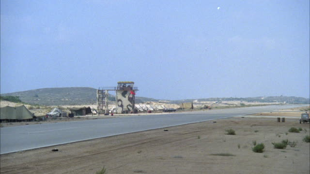 WIDE ANGLE OF MILITARY RUNWAY WITH CAMOUFLAGED CONTROL TOWER IN BACKGROUND. F-16 FIGHTER JET FLIES ACROSS RIGHT TO LEFT OF SCREEN ABOVE RUNWAY. PANS LEFT TO FOLLOW JET. MIDDLE EAST.