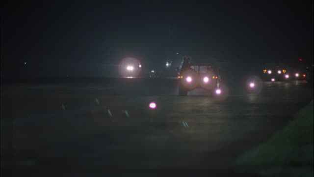 MEDIUM ANGLE OF TWO GREEN MILITARY JEEPS AND AIR FORCE ONE JET DRIVING TOWARD AND PAST CAMERA ALONG AIRPORT RUNWAY.