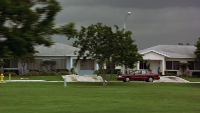 tracking shot of 1992 red chevrolet lumina left to right from across grass lawn yard or park. driving through middle class suburban neighborhood. - suburban stock videos & royalty-free footage