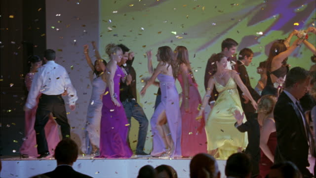 pan left to right of high school students or couples wearing evening gowns and tuxedos dancing in ballroom at school prom, dance, party or celebration. shapes and colors projected on movie screen in bg. flashing lights. - high school prom stock videos and b-roll footage