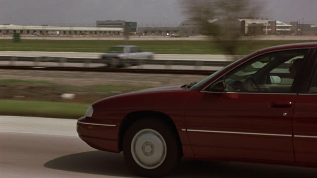 vidéos et rushes de driving pov on highway from passenger side. follows 1992 red chevrolet lumina. airport in background. see control tower and commercial planes and runway. traffic passes pov. - 2002