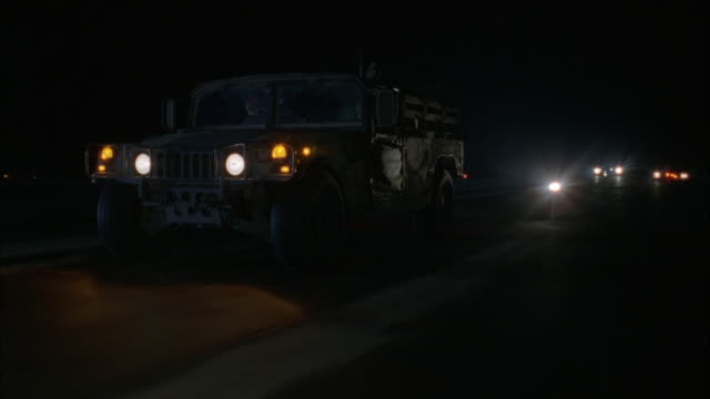 TRACKING SHOT OF GREEN MILITARY JEEP DRIVING ACROSS SCREEN FROM RIGHT TO LEFT ALONG RUNWAY. AIR FORCE ONE JET ENTERS SCREEN BEHIND JEEP FROM RIGHT AND TAKES OFF EXITING SCREEN TO LEFT.
