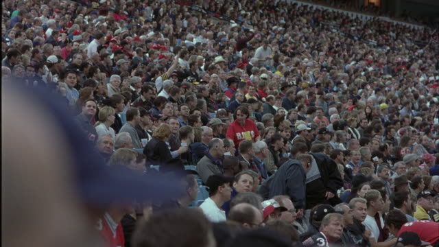 wide angle of crowd at stadium. could be football, baseball, basketball, or hockey game at sports arena. see people sitting and watching game. blurred baseball hat in foreground. - winter sport stock videos & royalty-free footage