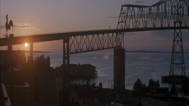 WIDE ANGLE OF BRIDGE OVER COLUMBIA RIVER IN OREGON. SUNSET. SEE BOATS DOCKED AT MARINA AND BUILDINGS ON RIVER EDGE. SEE CARS DRIVING ON BRIDGE. SEE STRIPS OF LAND IN DISTANCE ACROSS RIVER.