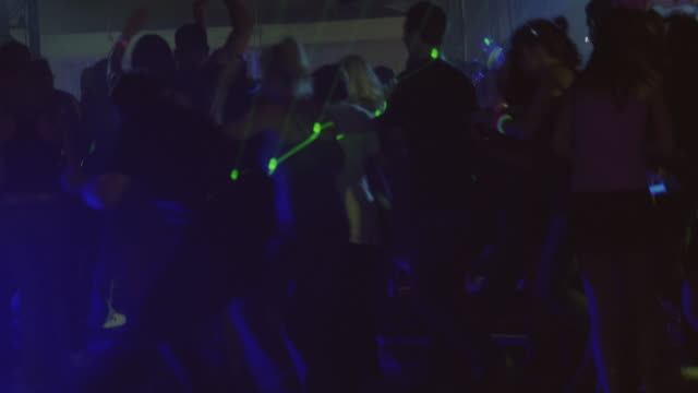 wide angle of dance party or rave party as dancers panic and run towards exits.  dancers are young adults, college aged. dancers duck and stoop as if being attacked by invisible creatures. - crowd running scared stock videos & royalty-free footage