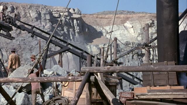 vídeos de stock, filmes e b-roll de medium angle of desert mine or quarry in mining town. see minors operating manual pulleys and conveyor belt. see miners with pick axes and wood mining scaffolds and equipment. - roldana