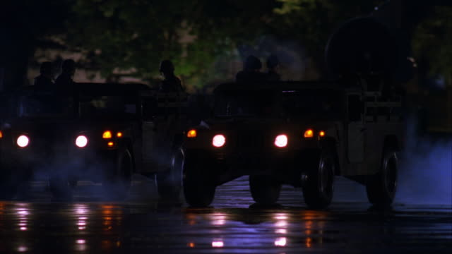 CLOSE ANGLE OF TWO JEEPS ESCORTING OR GUIDING AIR FORCE ONE ON AIR FORCE BASE OR AIRPORT. AIRPLANE TAXIES TO LEFT AS JEEPS SPLIT LEFT AND RIGHT. CAMERA TRACKS RIGHT JEEP AND TRACKS WHEELS OF AIRPLANE. HANDFUL OF SOLDIERS IN EACH JEEP. TARMACS. RUNWAYS.
