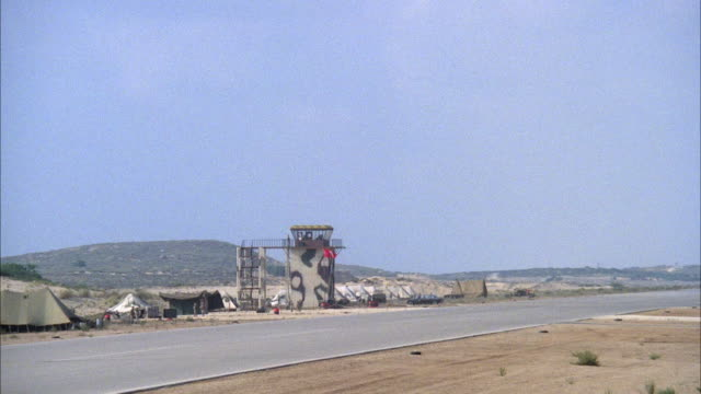 WIDE ANGLE OF MILITARY RUNWAY WITH CAMOUFLAGED CONTROL TOWER IN BACKGROUND. F-16 FIGHTER JET FLIES ACROSS RUNWAY TO LEFT. MIDDLE EAST.