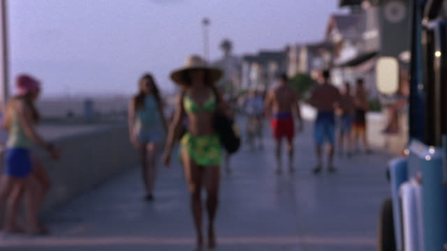 people in bathing suits walking on boardwalk in california. people holding surfboards and riding bicycles also on boardwalk. - running shorts stock videos & royalty-free footage