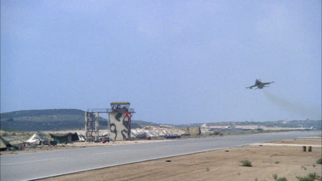 WIDE ANGLE OF MILITARY RUNWAY WITH CAMOUFLAGED CONTROL TOWER IN BACKGROUND. F-16 FIGHTER JET FLIES, BANKS TO RIGHT ACROSS RUNWAY TO LEFT. SLIGHT ZOOM IN OF CONTROL TOWER. MIDDLE EAST.