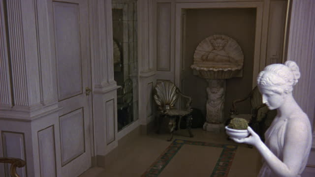 vidéos et rushes de medium angle of front entrance or foyer of upper-class apartment or hallway. see greek or roman style statue of woman holding bowl frame right. - stéréotype de la classe supérieure