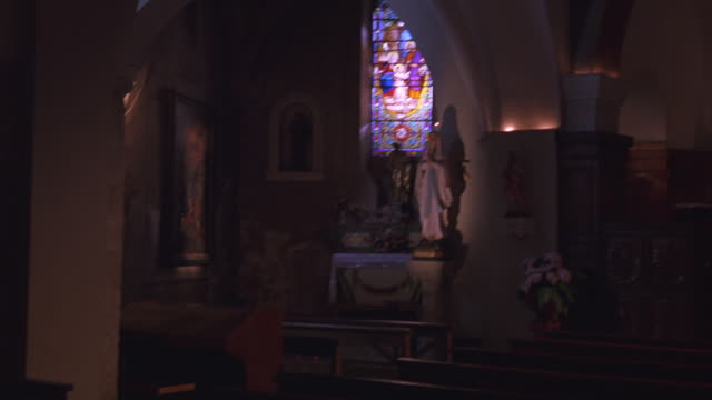 WIDE ANGLE WALKING POV THROUGH SANCTUARY OF CATHEDRAL OR CHURCH. PEWS. STAINED GLASS WINDOWS. ARCHED CEILINGS. RELIGIOUS STATUES AND ART. VIRGIN MARY. BURNING CANDLES ON ALTARS.