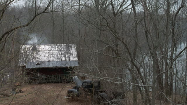 vidéos et rushes de medium angle of rundown, lower class, one story shack in forest. leaves on ground, probably fall or autumn. broken classic pickup truck parked in front of house. smoke coming from chimney. - cahute
