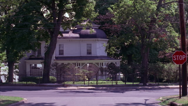 medium angle of white two story queen anne style victorian house surrounded by trees and t street intersection with stop sign in small town. red suv, white sedan, and tan sedan drive by. - zweistöckiges wohnhaus stock-videos und b-roll-filmmaterial