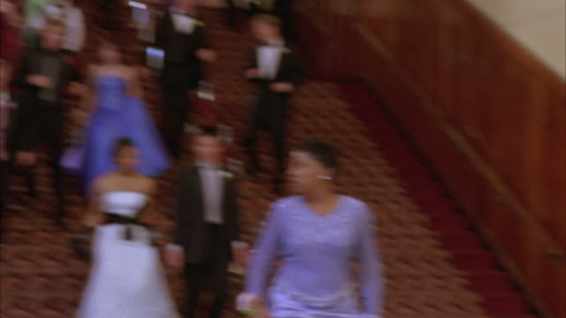steadicam of teenagers, high school students or couples wearing evening gowns and tuxedos leaving dance in hotel. crowd walking down staircase and through doors. unhappy reactions. could be end of dance. - evening gown stock videos and b-roll footage