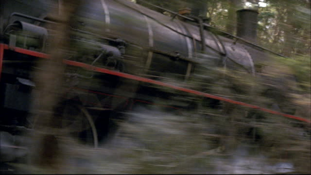 TRACKING SHOT OF BLACK STEAM ENGINE TRAIN IN FOREST. SEE STEAM RISING FROM TRAIN. SEE WHEELS OF BOXCARS AND ENGINE. SEE HILL OBSTRUCT POV OF TRAIN EXCEPT FOR TOP OF ENGINE. SEE BOXCARS AND WHEELS ROLLING ALONG RAILROAD TRACKS. SEE FOREST IN BACKGROUND.
