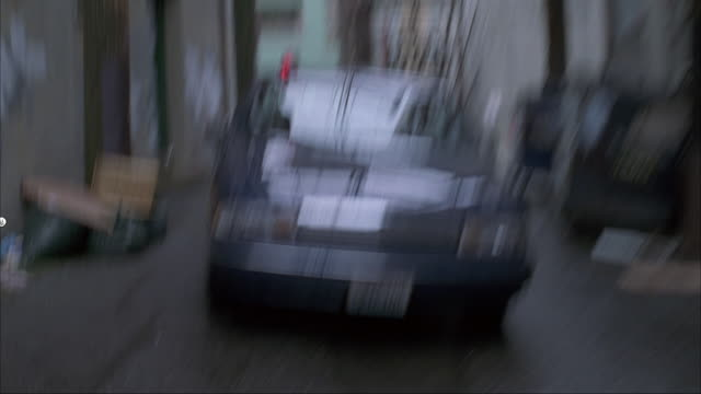 medium angle straight back moving pov of car chase. see front of blue car with siren flashing on top enter narrow alley, followed by brown car. cars pull out of alley crosses main street and enter another alley. - コート点の映像素材/bロール