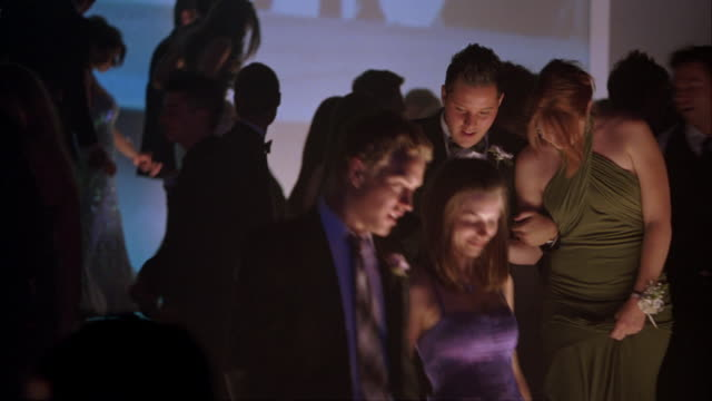 medium angle of high school students or couples wearing evening gowns and tuxedos leaving dance floor in ballroom at school prom, dance, party or celebration. shapes and colors projected on movie screen in bg. - ballroom stock videos & royalty-free footage
