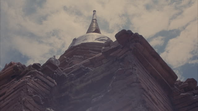 up angle of stone temple or shrine spire.  time lapse with clouds passing overhead, some sun halations. brick buildings. - spire stock videos & royalty-free footage