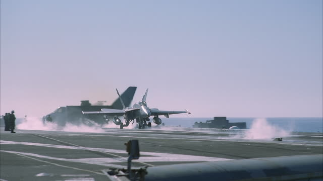 vidéos et rushes de medium angle of f/a-18 hornet on deck of ship. see white smoke curling up from deck. see blue sky. ocean glittering in bg. workers on deck prepare for jet take-off. - navire
