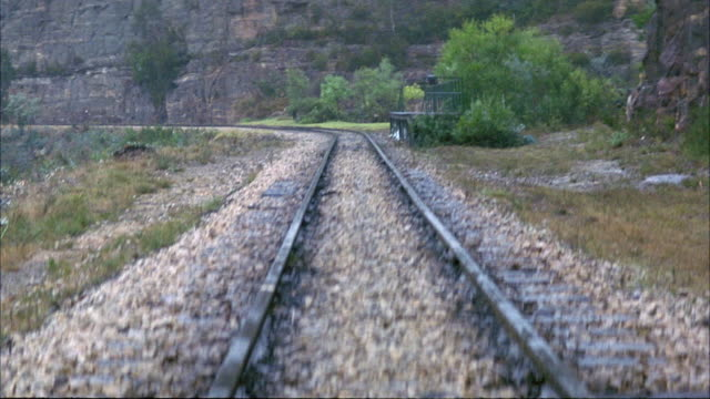 MEDIUM ANGLE OF RAILROAD TRACKS. SEE GRAY ROCK WALL ON LEFT. SEE GRAVEL AND GRASS NEXT TO RAILROAD TRACKS. SEE BLACK STEAM ENGINE TRAIN ENTER POV IN BACKGROUND.