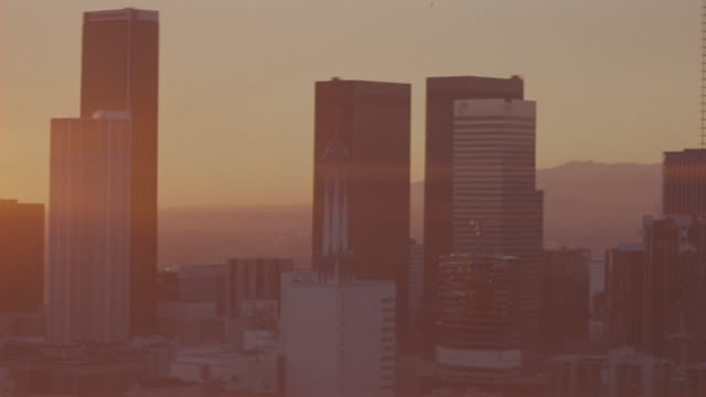 aerial of los angeles skyline at sunset. construction of skyscraper in center of downtown los angeles. see sun halations reflect on lens in far background along horizon. - anno 1983 video stock e b–roll