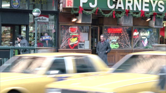 medium angle of sidewalk and storefront on busy street. see several taxis driving past in foreground. see a man dressed in a santa claus costume climb up stairs from subway and enter liquor store. christmas. - anno 1995 video stock e b–roll