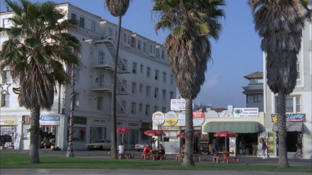 zoom in of venice beach possibly the strand, see sand and grass in foreground, palm trees, stores or possibly restaurants, and picnic tables. zooms in on white building on left, could be hotel, apartments, offices. - venice beach stock videos & royalty-free footage
