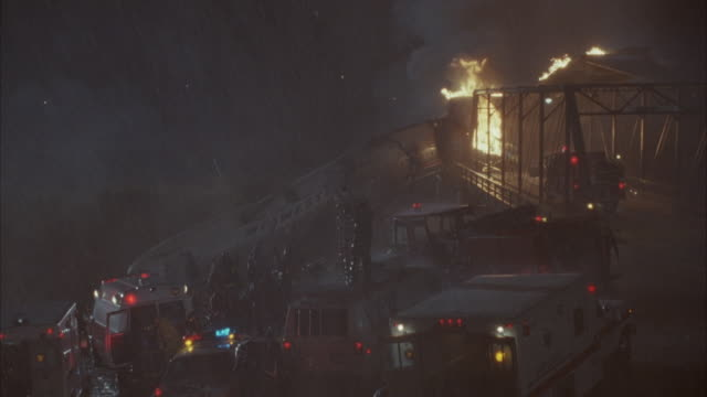 medium angle of wrecked plane or commercial airliner on ground and on fire surrounded by emergency vehicles including ambulances and fire trucks. see news van among vehicles. raining. - 航空事故点の映像素材/bロール