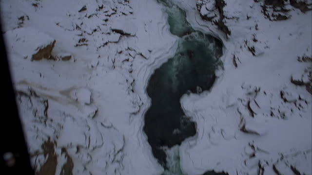 aerial of rear-view, high angle down pov from helicopter flying through snowy mountain gorge in winter. see ice and open water in partially frozen river below. - ravine stock videos & royalty-free footage