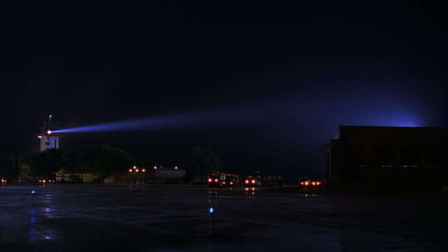 WIDE ANGLE OF CONTROL TOWER WITH SPOTLIGHT FLASHING RIGHT IN AIR FORCE BASE OR AIRPORT. CONTROL TOWER ON LEFT. AIR FORCE ONE AIRPLANE TAXIES FROM RIGHT TO LEFT, AND SPOTLIGHT TRACES AIRPLANE.