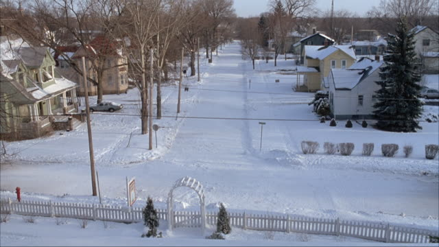 HIGH ANGLE DOWN OF RESIDENTIAL AREA COMPLETELY BLANKETED WITH SNOW. SEE STREET, SIDEWALK, LAWNS AND ROOFS ALL COVERED WITH SNOW. SEE COUPLE PEOPLE SHOVELING SNOW OR WALKING DOWN SIDEWALK IN BACKGROUND. SEE WHITE FENCE AND ARCH IN FOREGROUND.