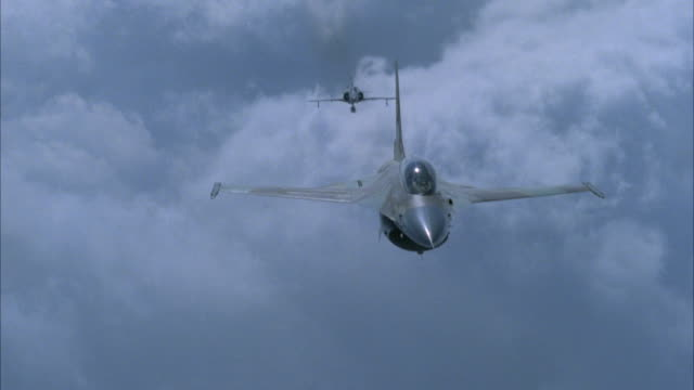 medium angle straight back moving pov of front of dog fight between camouflaged f-16 fighter and kfir jet or airplane. jets  bank left and right. cloudy day. neg cut. action. - fighter stock videos & royalty-free footage