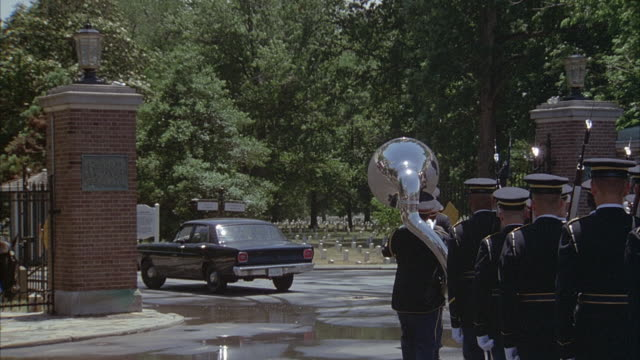 medium angle of military funeral walking through gates at arlington national cemetery. military band marches through gates behind black ford, then caisson comes behind soldiers. four black cadillac coupe de villes drive through gate at end. - アーリントン点の映像素材/bロール