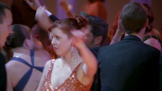 pan right to left of high school students or couples wearing evening gowns and tuxedos dancing in ballroom at school prom, dance, party or celebration. shapes and colors projected on movie screen in bg. flashing lights. - high school prom stock videos and b-roll footage