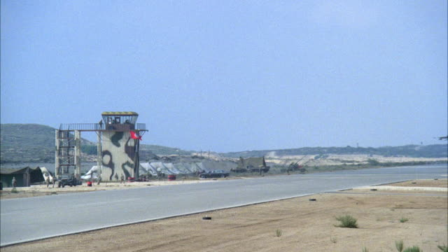 WIDE ANGLE OF MILITARY RUNWAY WITH CAMOUFLAGED CONTROL TOWER IN BACKGROUND. F-16 FIGHTER JET LOWERS TO LAND AND FLIES ACROSS RUNWAY TO LEFT. SEE SOLDIERS MOVING IN BACKGROUND NEAR CONTROL TOWER. MIDDLE EAST.