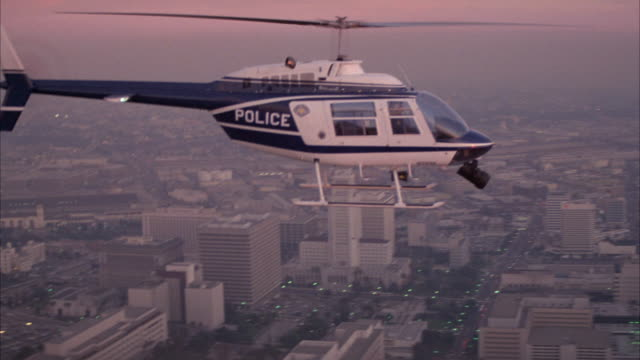 aerial of police helicopter flying over city and downtown area. passes high rise office buildings, one which reads first interstate and one which reads crocker bank. - autostrada interstatale americana video stock e b–roll