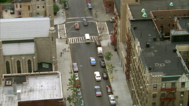 AERIAL OF A BLUE POLICE CAR DRIVING DOWN A ONE WAY STREET WITH HIGH RISE APARTMENT BUILDINGS LINING STREET. SEE CARS PARKED BUMPER TO BUMPER ALONG CURBS. SEE STREET CURVE AROUND.