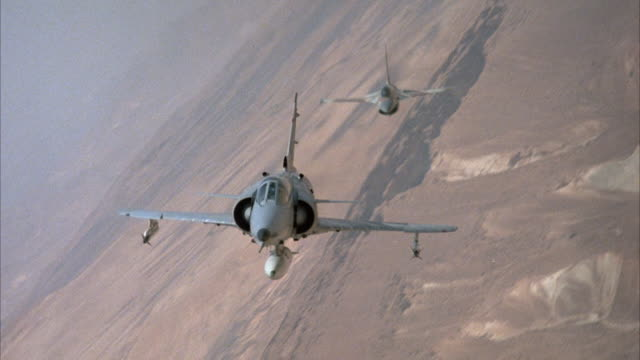 MEDIUM ANGLE FRONT POV OF KFIR JETS AND CAMOUFLAGE F-16 FIGHTER AIRPLANES ENGAGED IN DOGFIGHT. ARID AREA OR DESERT ON GROUND. ACTION. MIDDLE EAST.