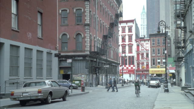medium angle looking down city street. see five story apartment buildings on both sides of street. see street end into cross street in distance. see pedestrians on sidewalks. see skyscrapers in background. - anno 1999 video stock e b–roll