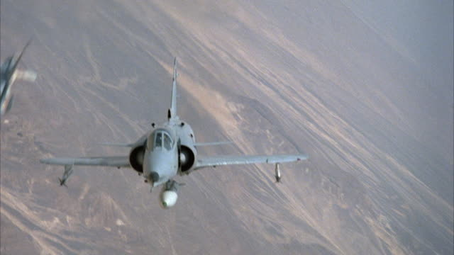 MEDIUM ANGLE FRONT POV OF KFIR JETS AND CAMOUFLAGE F-16 FIGHTER AIRPLANES ENGAGED IN DOGFIGHT. TRAILING JET PERFORMS BARREL ROLLS AND EXITS FRAME. ARID AREA OR DESERT ON GROUND. ACTION. MIDDLE EAST.