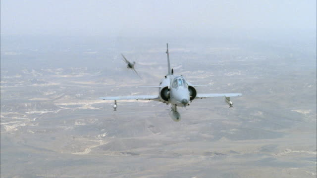 MEDIUM ANGLE OF FRONT OF CAMOUFLAGE F-16 FIGHTER AND KFIR JETS OR AIRPLANES ENGAGED IN DOGFIGHT. TRAILING JET PERFORMS BARREL ROLL AND EXITS FRAME TO TOP. ACTION. MIDDLE EAST.