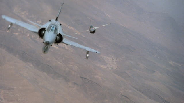 medium angle front pov of kfir jets and camouflage f-16 fighter airplanes engaged in dogfight. arid area or desert on ground. action. middle east. - fighter stock videos & royalty-free footage