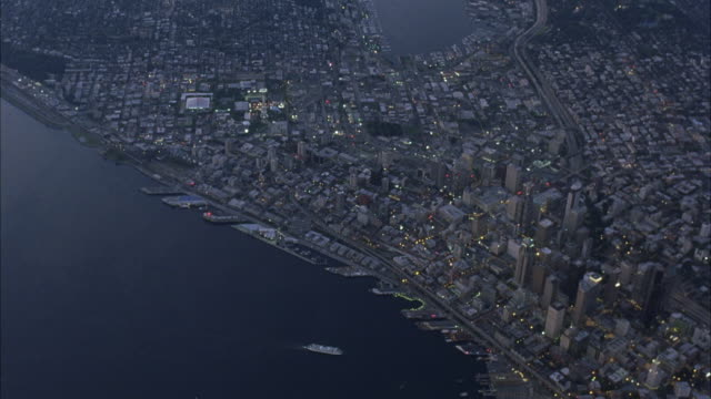 vidéos et rushes de aerial flying over seattle and puget sound and coastline. could be peninsula or island. see downtown area and two boats in ocean. camera flies down between high rise buildings. see train and cars. could be dusk or dawn. - seattle